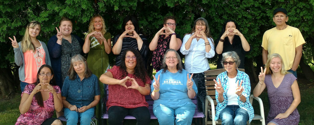 group of people make hearts and peace signs with their hands